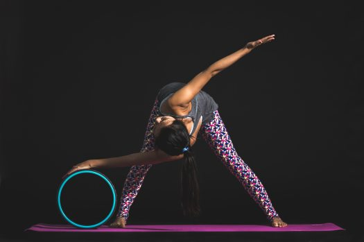 Woman doing a twist on a yoga wheel with a black background