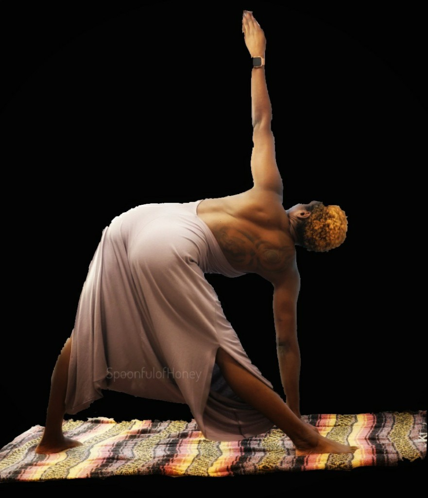 Picture of woman with black background practicing trikonasana